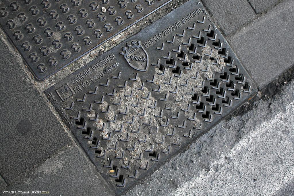 Une plaque de fonte au sol. Le nom de la fonderie y est inscrit.