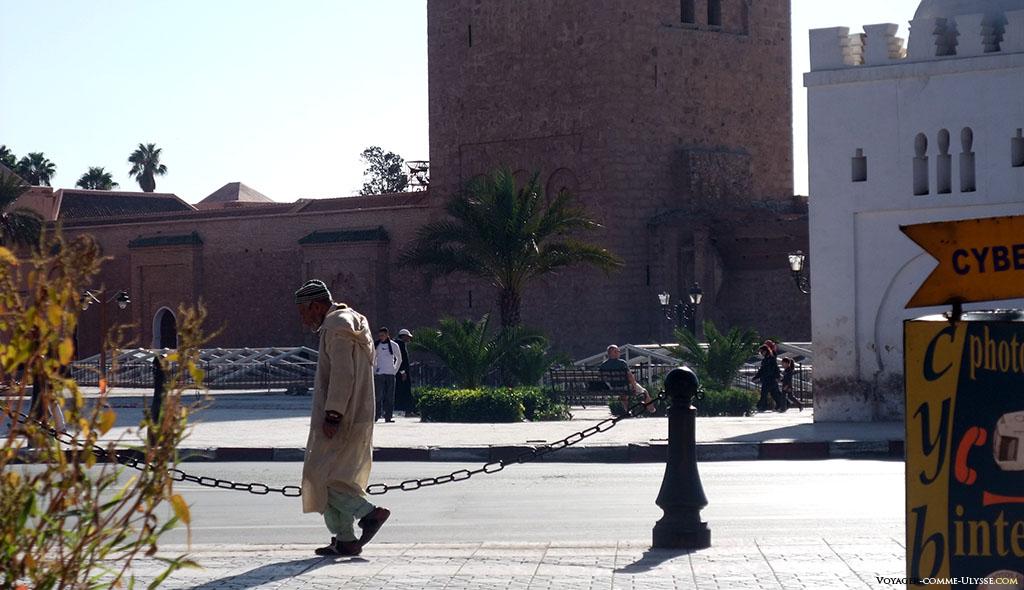 Cette personne âgée marche avec le dos voûté, en costume traditionnel.