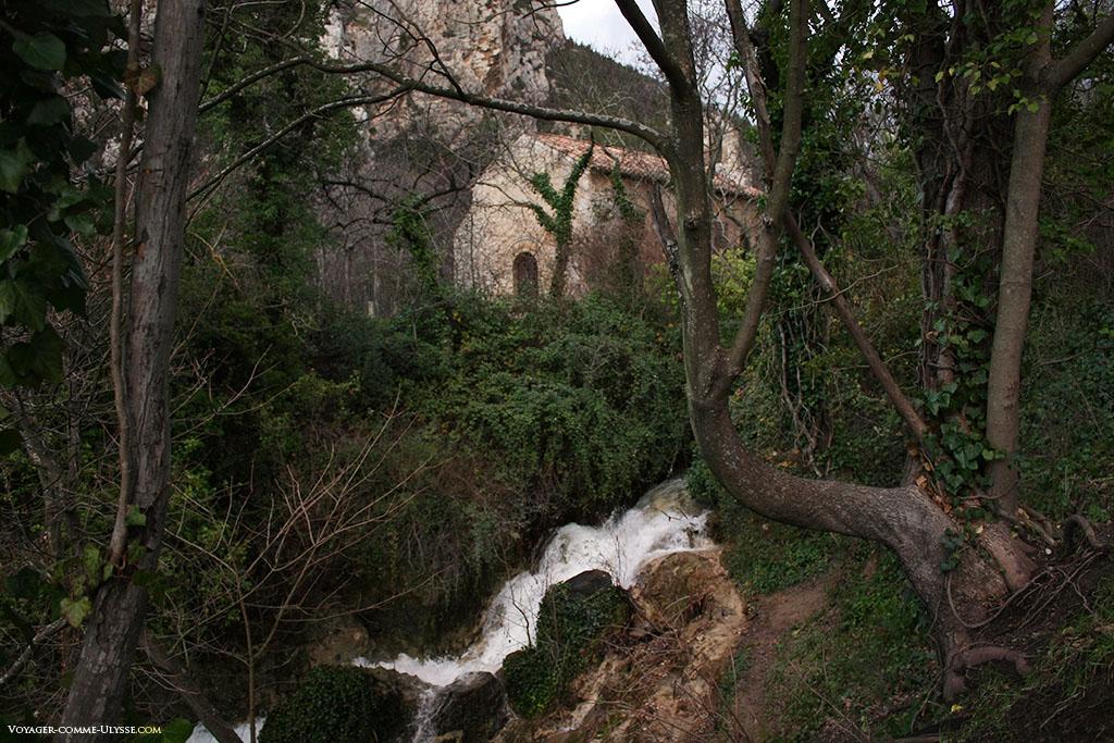 Derrière les arbres et la petite cascade, on aperçoit l'ancienne église