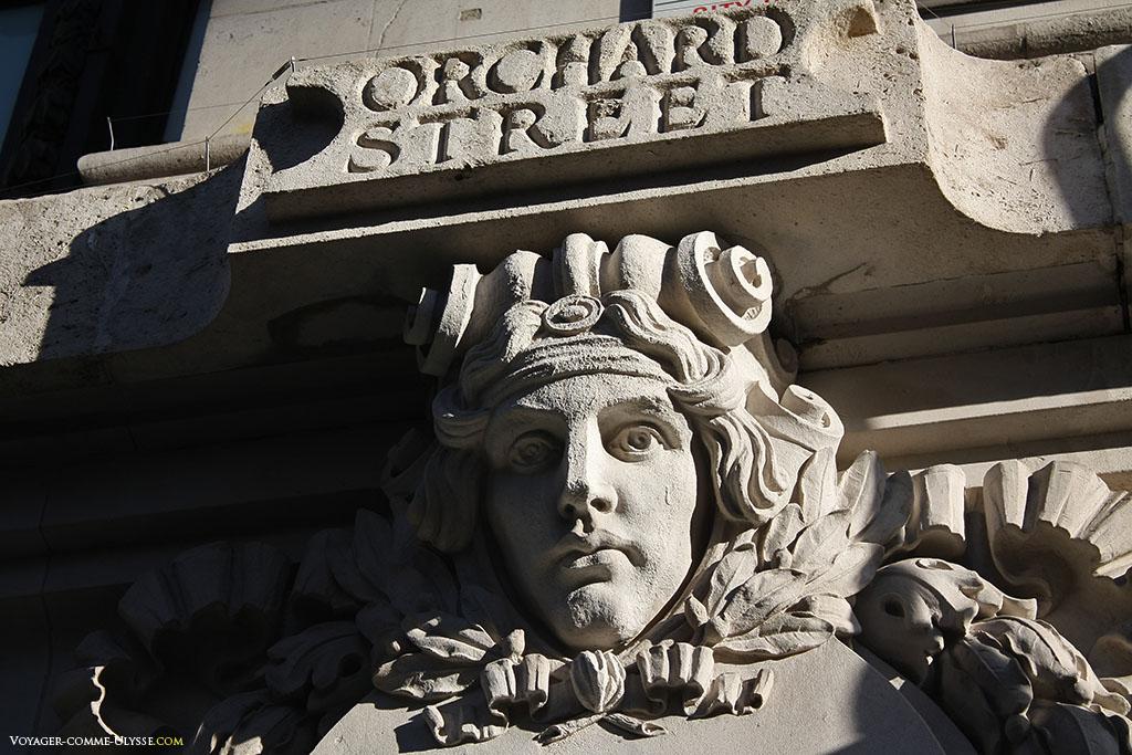 Un beau visage de pierre, à coté de la plaque d'Orchard Street, sur le bâtiment de Selfridges.