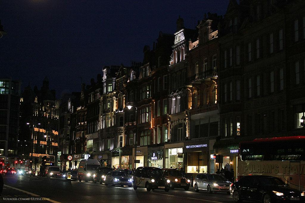 Succession d'immeubles et leur boutiques au rez-de-chaussée, illuminées pour la nuit.