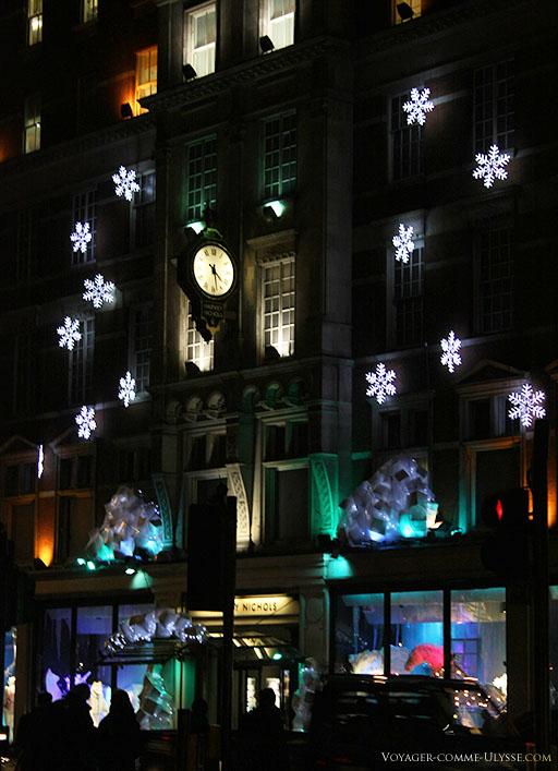 Une façade d'immeuble, joliment décorée avec des flocons de neige lumineux.