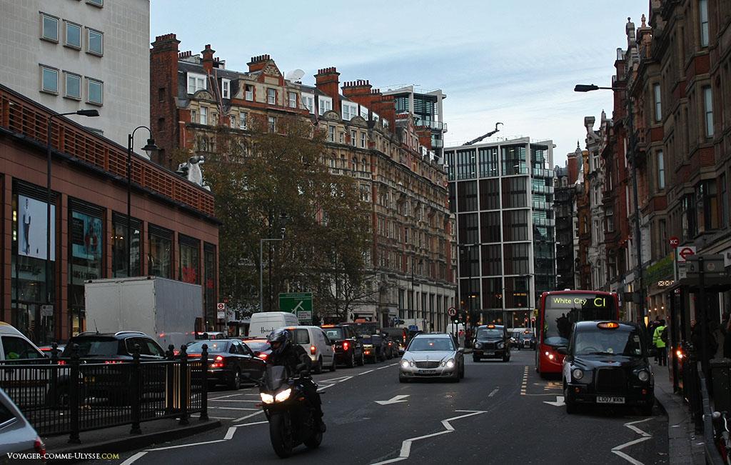 Une grande typiquement londonienne, avec les magasins, le mélange de styles, la circulation, les bus, les taxis... toute l'agitation d'une très grande ville.