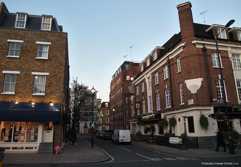 Une rue typique de Londres, avec ces petits immeubles de brique et ses fenêtres blanches à carreaux, sans volets.