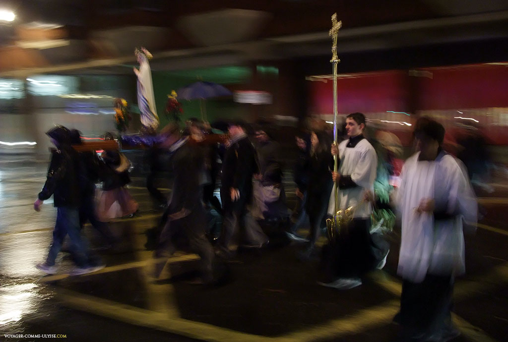 Procession de catholiques, par une nuit pluvieuse. Les catholiques semblent ne pas hésiter à s'afficher dans un pays majoritairement protestant.