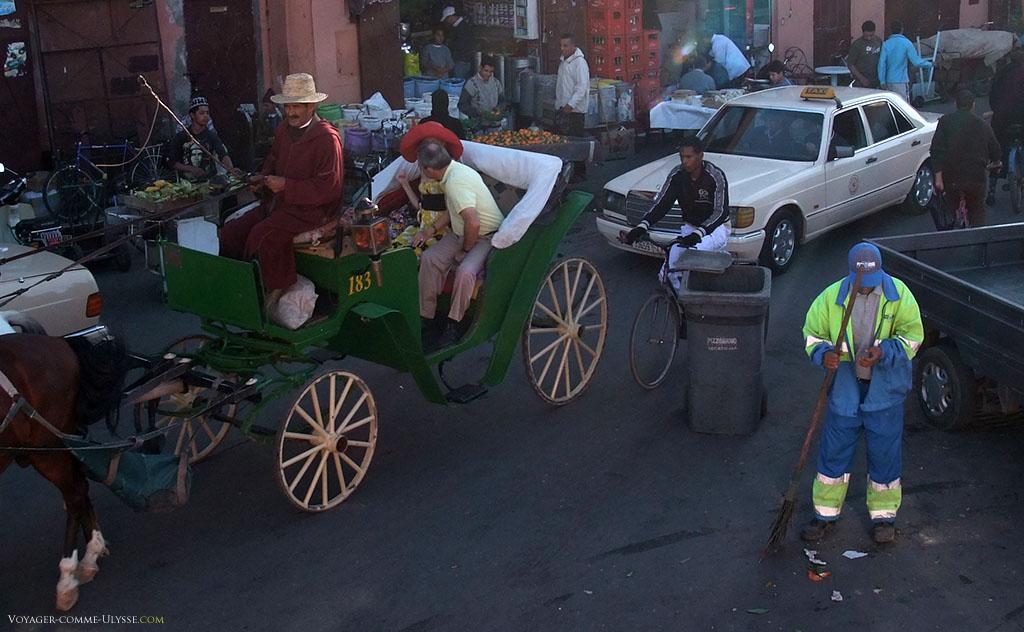 On distingue très bien le balayeur de rues de Marrakech, avec ses habits colorés, menant à bien tranquillement son travail avec sa poubelle, au beau milieu de la circulation automobile ou de calèches.