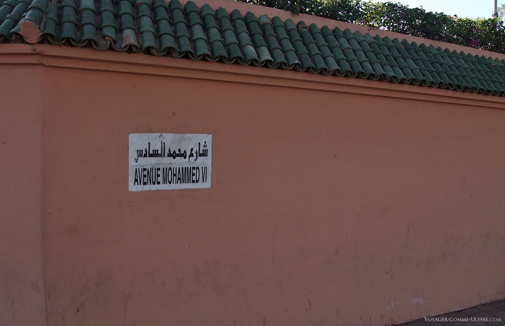 Sur un mur, la plaque indiquant l'avenue Mohammed VI, peinte.