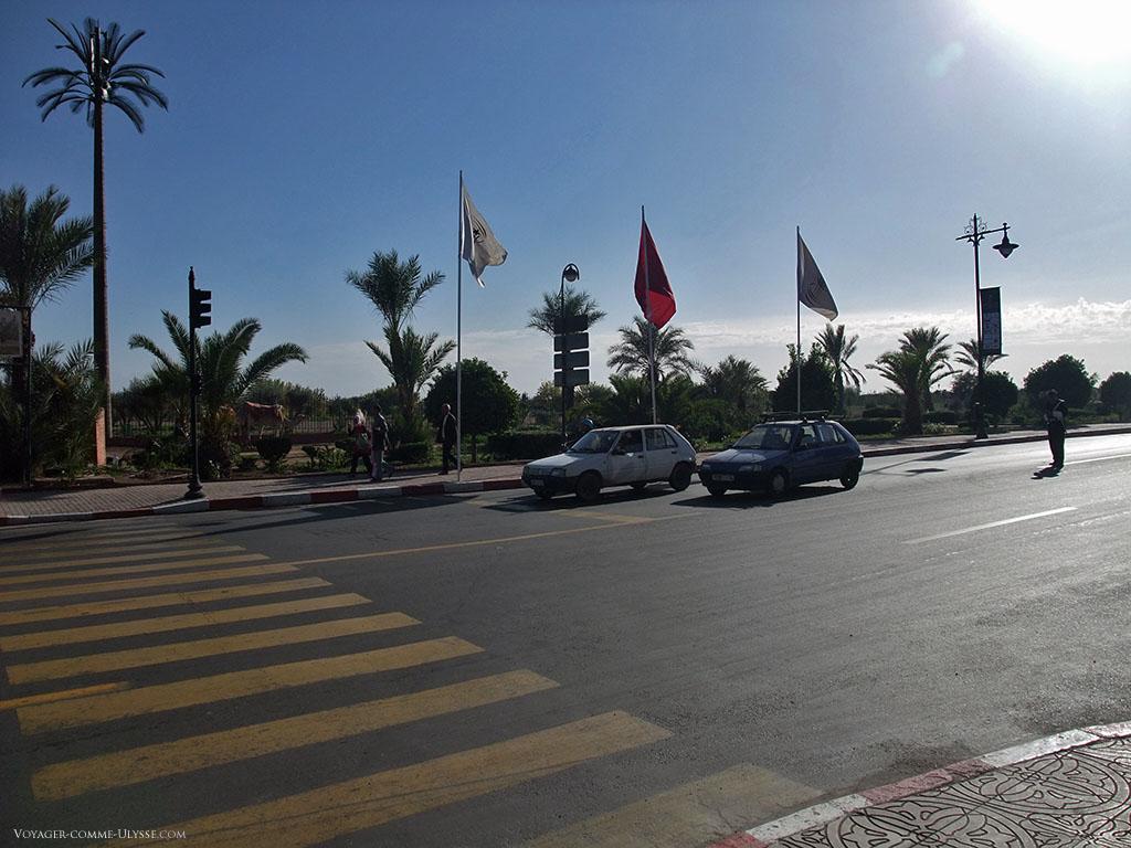 Arrêtons nous un instant sur cette photo à priori anodine, et regardons les détails urbanistiques de Marrakech. Les passages piétons sont jaunes, peut-être pour ne pas éblouir les passants si ils avaient été blancs? Regardez le bout de trottoir en bas à droite, ils sont décorés avec des motifs géométriques. Tout en haut du palmier à gauche, vous avez des antennes de téléphonie mobile, et, à droite, un policier avec son bel uniforme aux gants blancs, régulant la circulation.