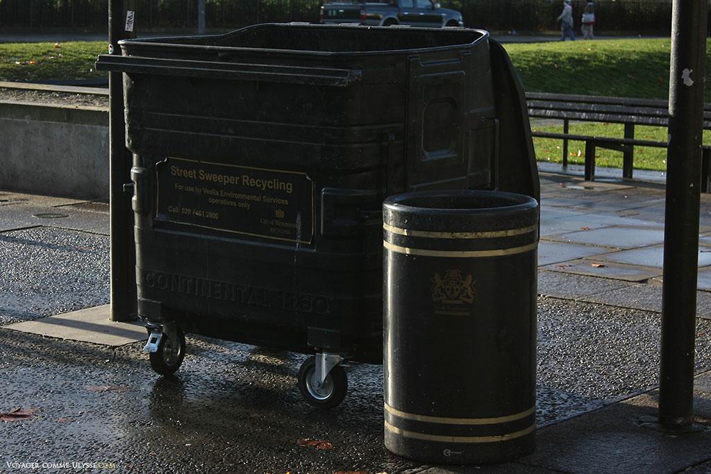 Deux exemples de poubelles: à gauche, une grande benne à ordures, où les balayeurs viennent jeter les feuilles mortes. A droite, une simple poubelle, dans un ton sobre cerclé de bandes dorées. Notez les armoiries, cet objet est beau!