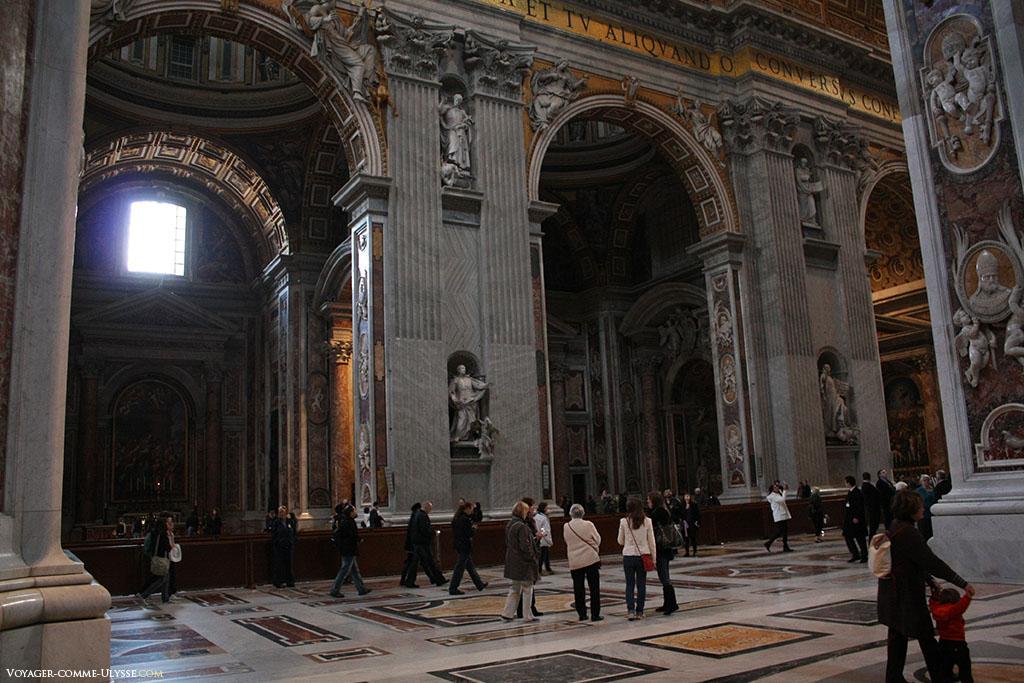 L'oeuvre de Maderno est proportionnelle à celle de ses prédécesseurs : colossale. Cet nef est immense, et abondamment décorée. Des inscriptions sur fond doré font le tour de la basilique.