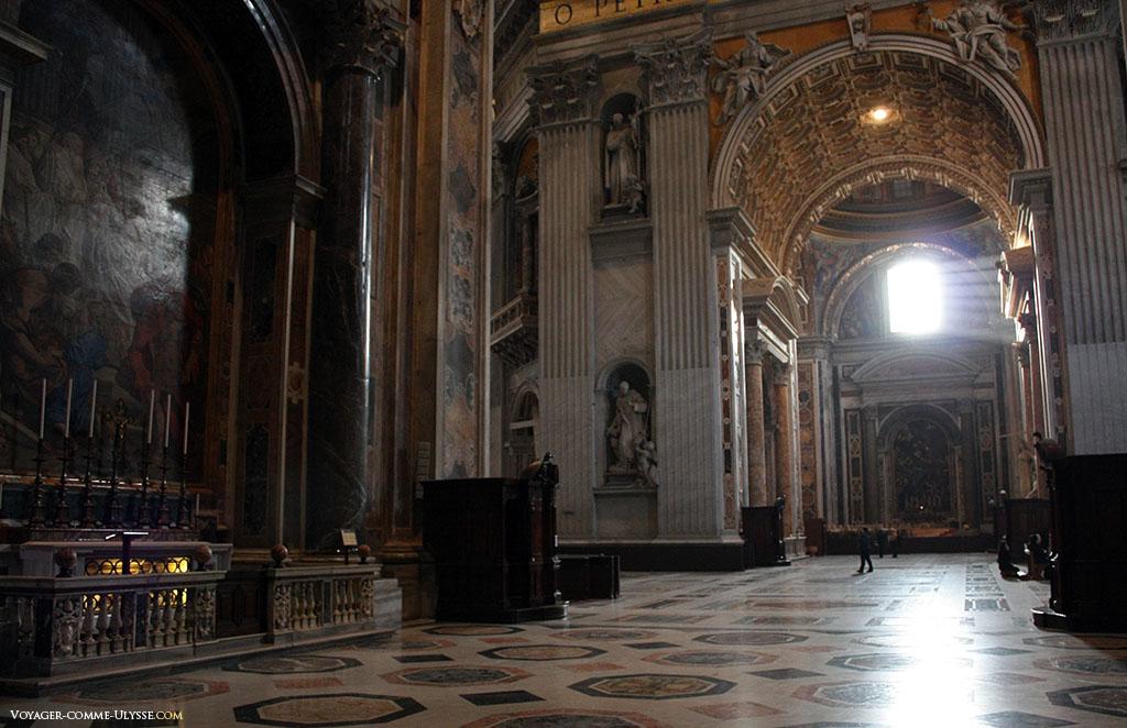 Veja o pequeno tamanho das pessoas que passeiam ao fundo, postos em relação com o gigantismo da basílica. Os raios de luz penetram pelas grandes janelas, contudo, insuficientes para serem invadidas pelo sol, contribuindo para a criação da atmosfera muito particular da grande basílica.