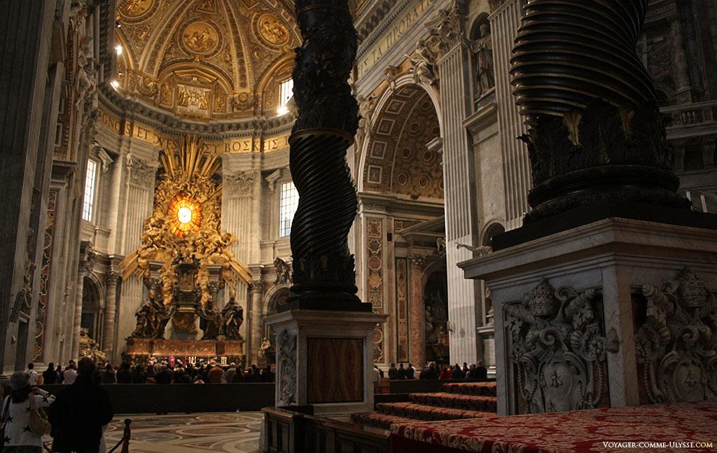 Em primeiro plano, as colunas torcidas do baldaquim. Ao fundo, a Cadeira de São Pedro dentro da abside.