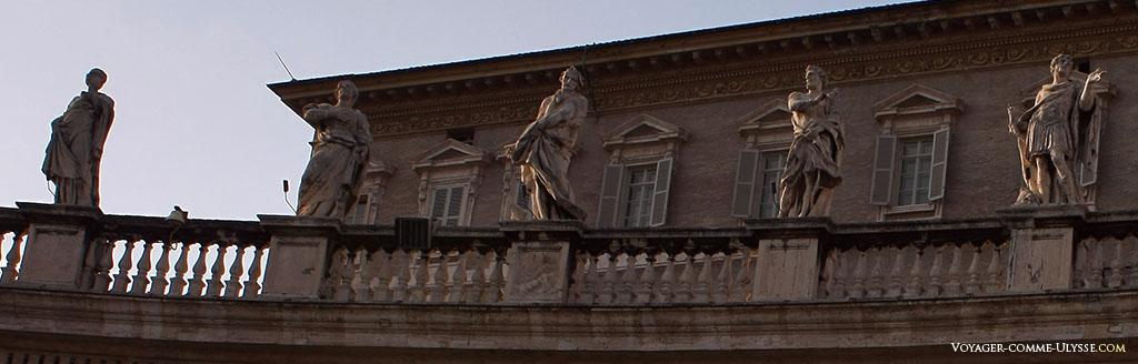 Algumas estátuas por cima da colunata de Bernini. Por detrás, o Palácio Apostólico.