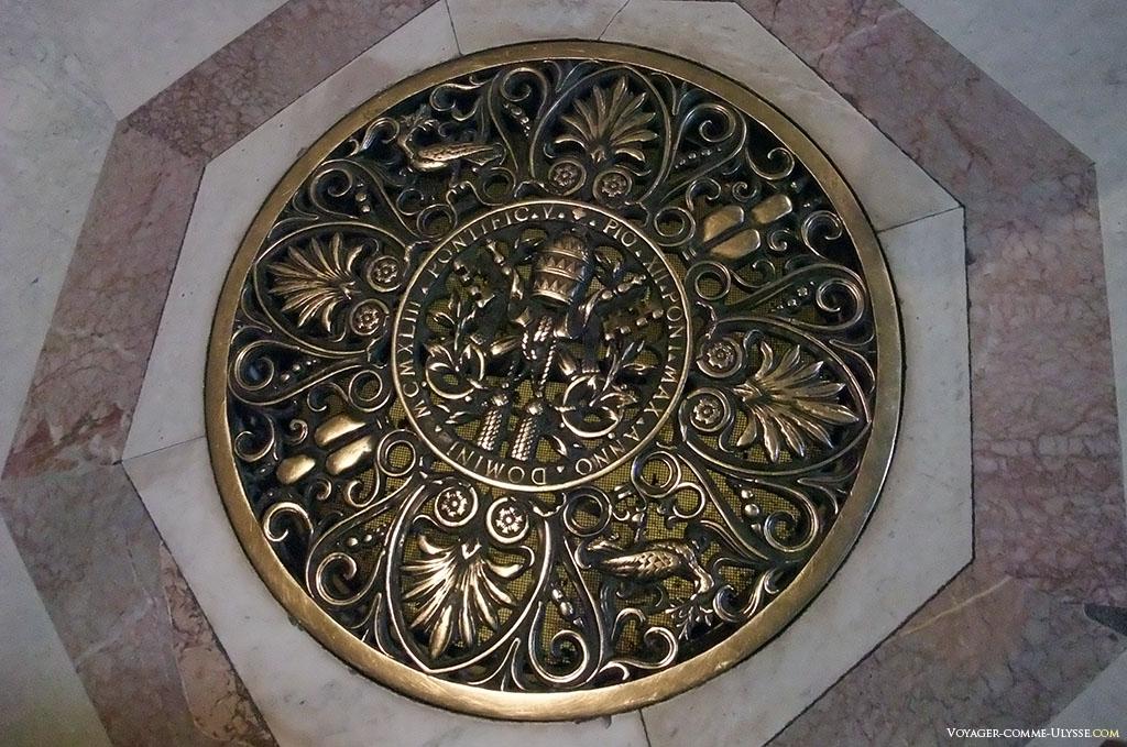 Une bouche d'aération au sol de la basilique, magnifiquement travaillée, avec les armes de Pie XII.