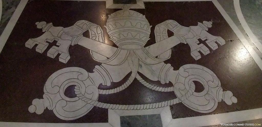 Os símbolos do papado, com as chaves de São Pedro, inscritas na pedra sobre o solo.