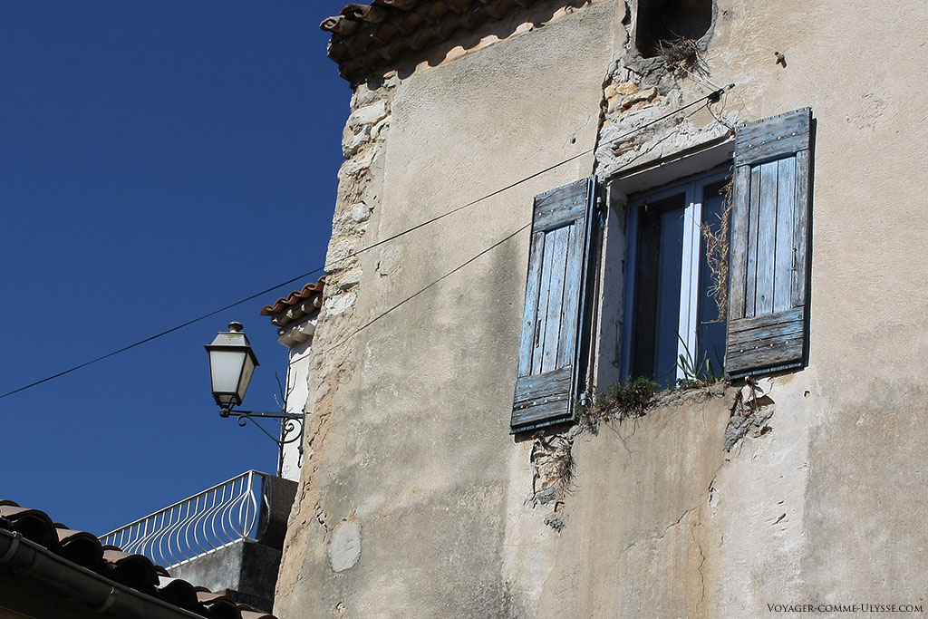 Même avec un mur fissuré, sous un ciel bleu avec des volets bleus, il semble beau, vous ne trouvez pas?