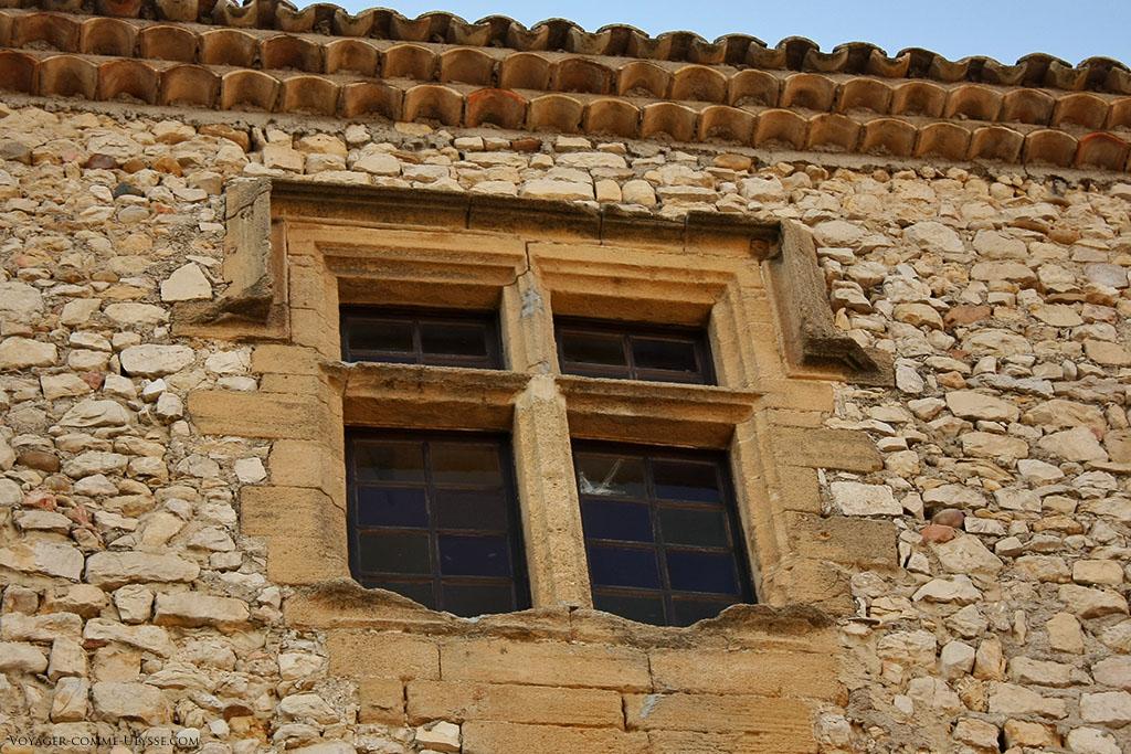 Fenêtre à meneaux, perçant l'épais mur de pierre d'une maison du village.