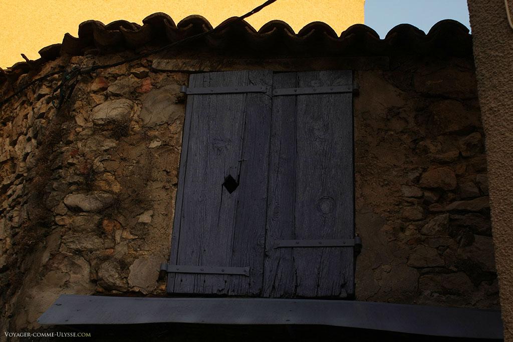 Cette visiblement très ancienne fenêtre a elle aussi des volets bleus.