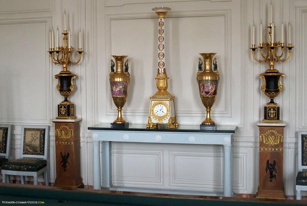 As cadeiras estão tapadas pela tapeçaria de Beauvais. Ao centro, um relógio de coluna em porcelana de Sèvres.