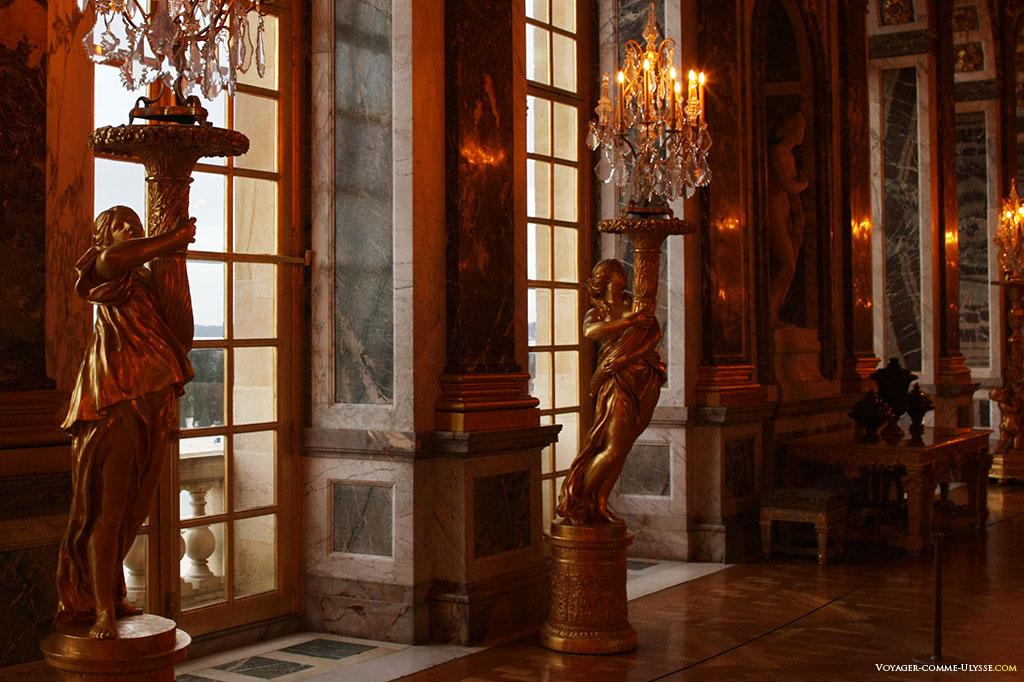 Mulheres com archotes na Galeria dos Espelhos. Elas têm um candelabro para iluminar o quarto.
