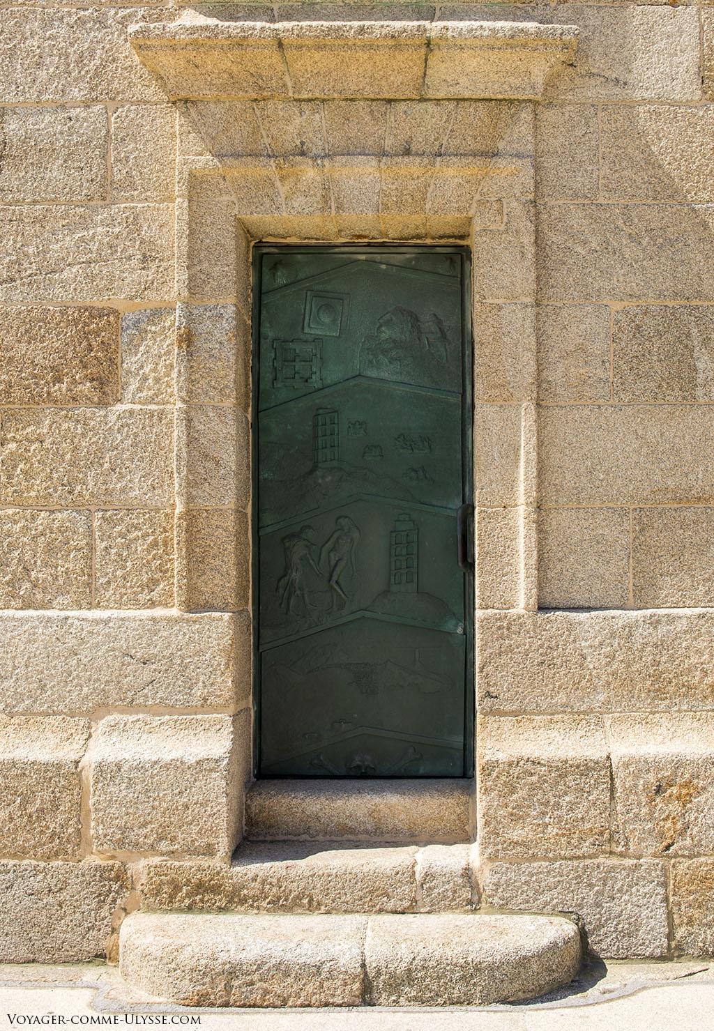 Solide porte de bronze, avec dessus les bas-relief de la tour.