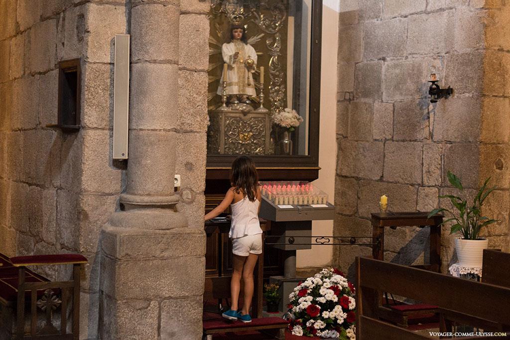 Na igreja da Corticela encontramos uma imagem do menino Jesus de Praga. Aqui, uma pequena menina no gesto para ligar as velas elétricas.