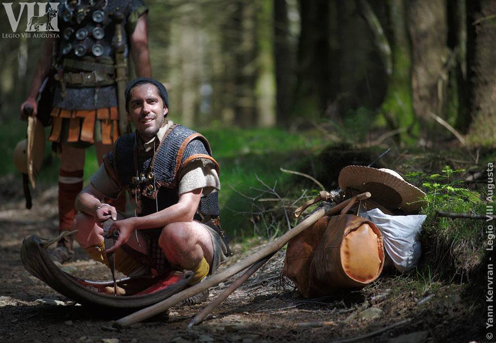 Une petite pause pour réparer une sangle de bouclier, après plusieurs heures à marcher, avec tout l'équipement d'un légionnaire romain.
