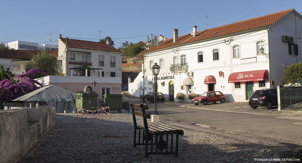 grande rue d'Abiul, avec à gauche les poubelles et de l'autre coté de la rue la banque et le bar