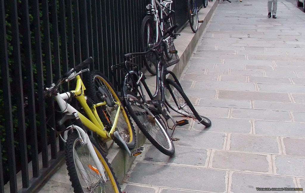 Vélos stationnés, plus ou moins vandalisés, et attachés comme on peut à la grille du square.