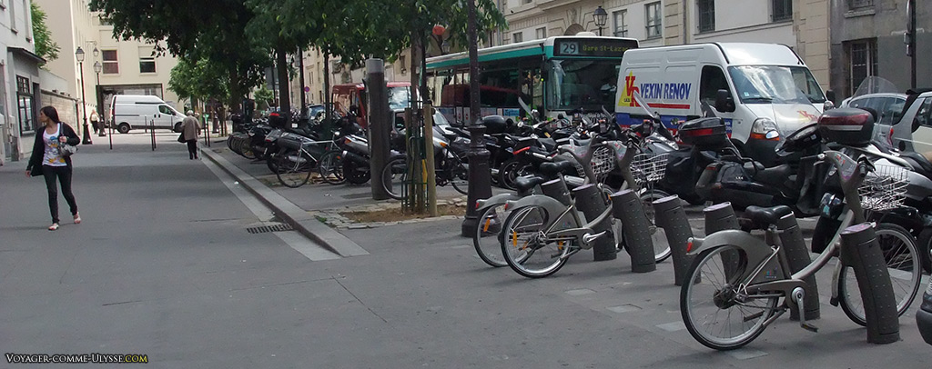 Une station vélib, squattant un large trottoir de Paris.
