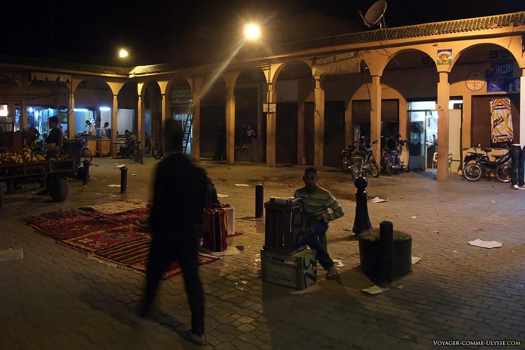 Le marché se termine, mais il reste encore quelques vendeurs. Tout à gauche, un vendeur de bananes, et à droite, un jeune vendeur de cigarettes.
