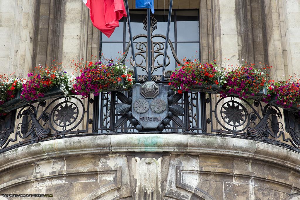 Sur le balcon en fer forgé de l'hôtel de ville, les deux distinctions de la ville : Croix de Guerre et Légion d'Honneur.