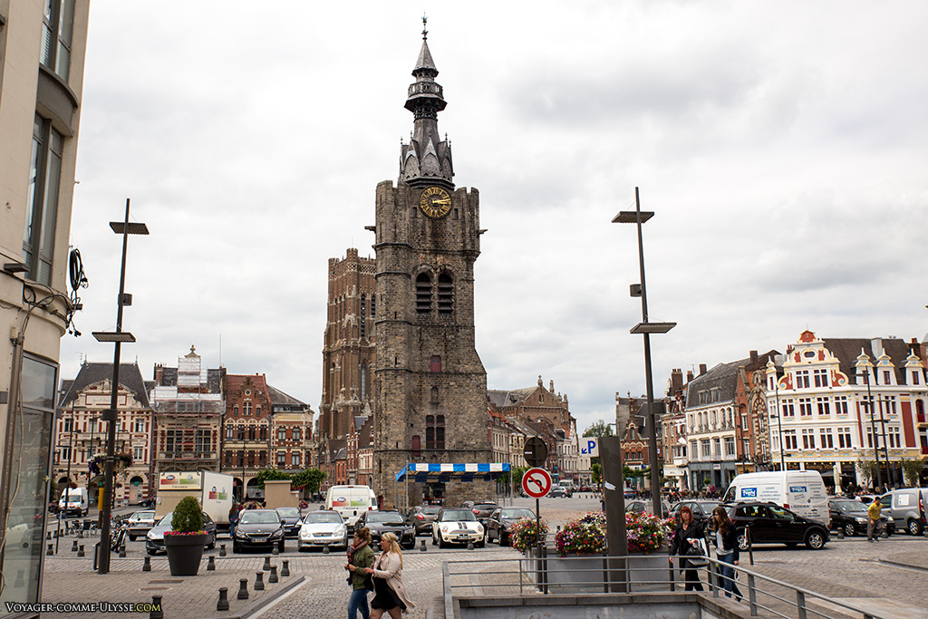 Le beffroi trône au centre de la Grand Place. On remarque l'entrée du parking au premier plan.