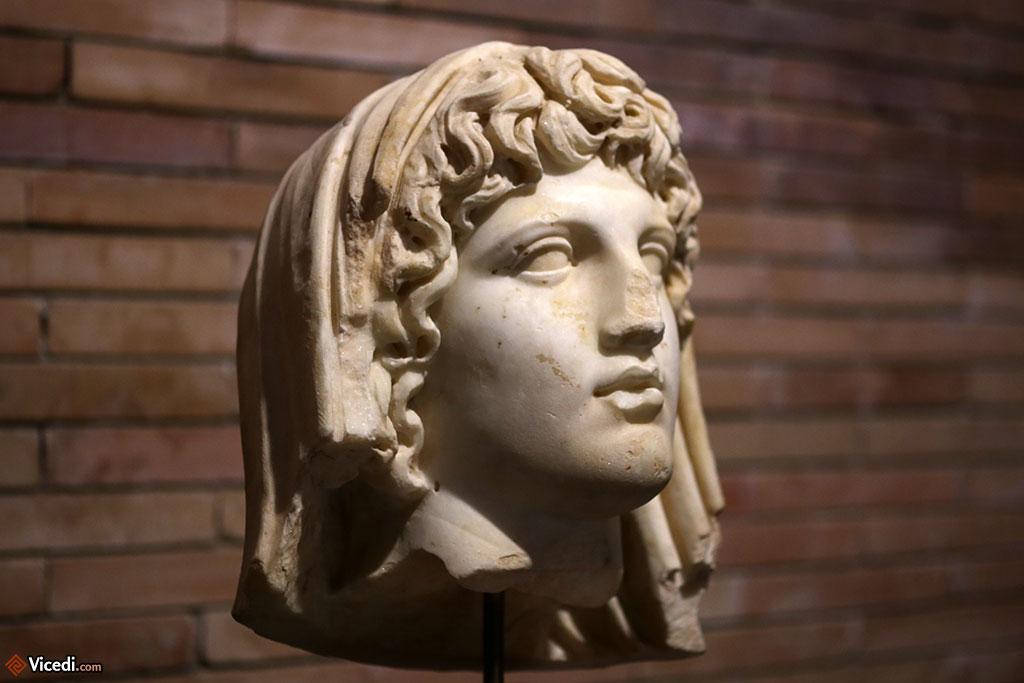 Tête du génie de la colonne. Il s'agit d'une divinité tutélaire de la ville, retrouvée sur le forum municipal. Ier siècle.