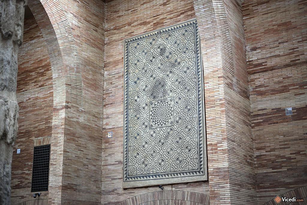 Plaquée contre le mur et en hauteur, cette mosaïque est à la fois protégée des passants et visible par tout le monde.