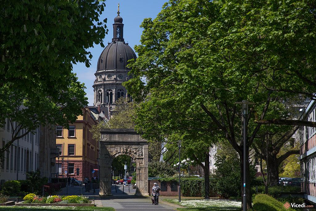 On peut voir la reproduction de l'arc de Dativius Victor, un dirigeant de Mogontiacum. Au fond, derrière, l'église du Christ, Christuskirche, une église protestante inaugurée en 1903.