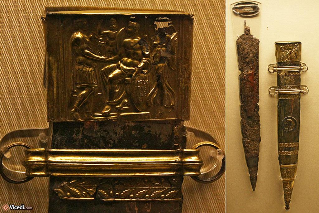 Le glaive de Mayence, conservé au British Museum. Il est également connu sous le nom d'épée de Tibère. A gauche, un détail du fourreau, où l'on peut voir Tibère céder la victoire à Auguste. La déesse de la Victoire est représentée par une statuette.