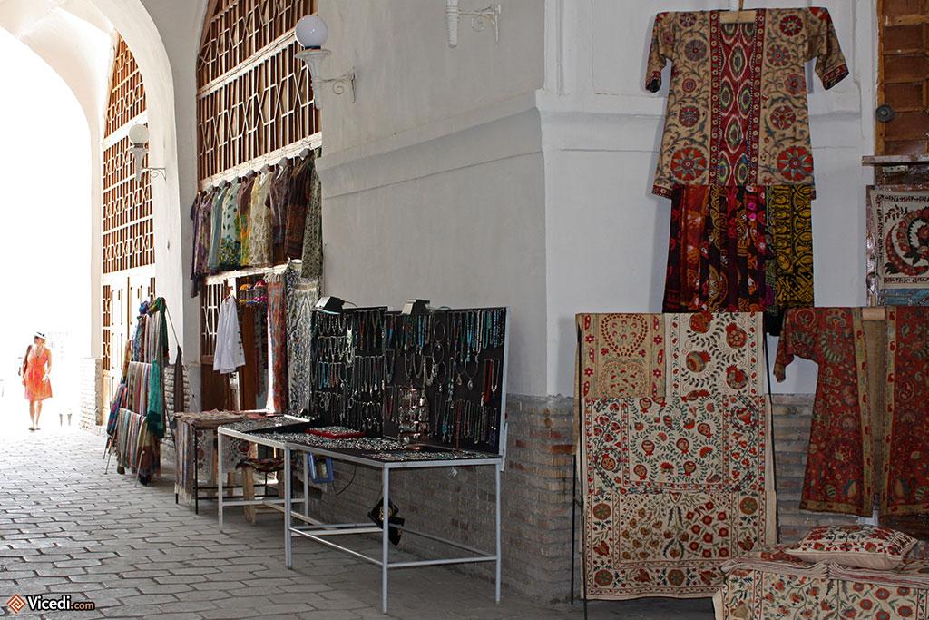 Dans une ancienne coupole de Boukhara, on y fait toujours du commerce : on peut y voir des suzanis à droite.