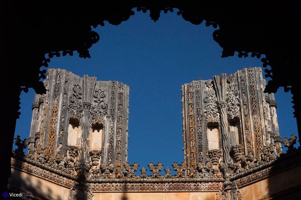 Vue sur deux des piliers inachevés, avec en ombre chinoise le portail principal Manuélin.