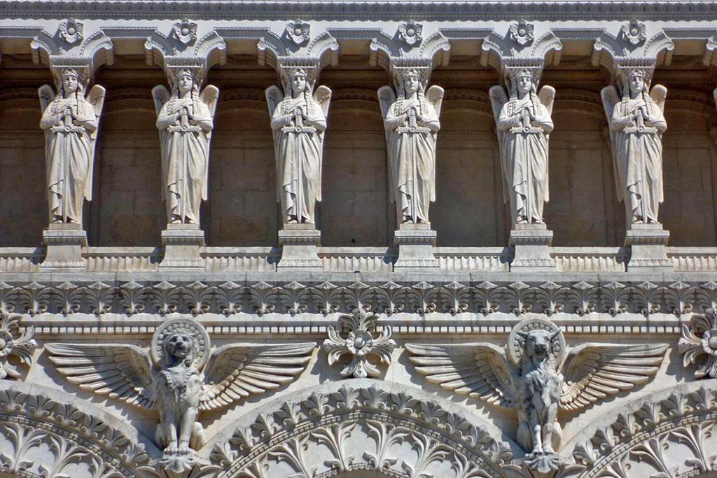 Détail de la façade, avec les cariatides en haut, et deux des symboles des évangélistes en bas.